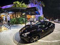 Black Ferrari car in front of Pier 22 restaurant at night along the Riverwalk on the Manatee River in Bradenton Florida.