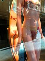Mannequin wearing sexy lingerie and its reflection on mirror in a shop window. Spain.