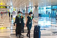 Singapore, Republic of Singapore, Asia - Upon their arrival at Changi Airport, flight attendants of the Taiwanese airline Eva Air wear protective mask...