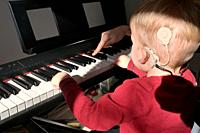 A Boy With A Hearing Aids And Cochlear Implants Playing Piano.