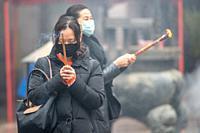 Shanghai, China, 23rd Jan 2020, Women wearing masks pray with burning joss sticks, Edwin Remsberg.