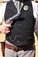 Close up of a US Marshal tin star and Colt Peacemaker revolver proudly displayed by reenactor at an event in Tucson AZ.
