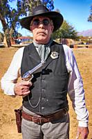 Reenactor wearing a US Marshal tin star and holding a Colt Peacemaker at an event in Tucson AZ.