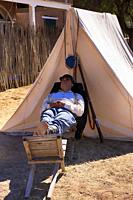 Soldier of the 1880s US Army 5th cavalry snoozing outside his tent at Fort Lowell in Tucson AZ.