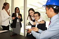 User experience page receiving house model from the architect's hands symbolically at the mortgage opening the work team encourages joy when applaudin...