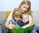 Mother reads a book with two children, boy and babygirl, Scania, Sweden.