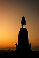 The Virginia Memorial at Gettysburg National Battlefield is rendered into silhouette at sunrise.
