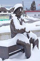 Hertage bronze statue of a fish cannery worker draped in a fresh fall of snow in the village of Steveston British Columbia.
