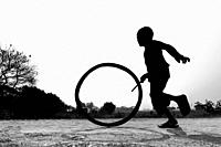 "Bangladesh â. "" January 24, 2020: A restless boy is playing on the village road with old discarded tires at Savar, Dhaka, Bangladesh."