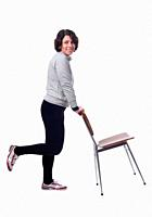 woman standing with a chair in white background.