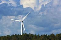 A wind turbine is turning its rotor blades above a green forest on a windy summer day with cumulus clouds.Västernorrland, Sweden, Europe.