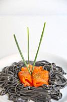Smoked salmon with black spaghetti and chives.