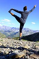 A woman practices yoga up the mountain in the Pyrenees, Spain