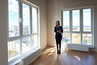 The girl with the folder stands in the middle of a large spacious room with large windows.