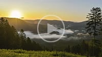moving fog fields and clouds at the sunrise in a valley of the Black Forest from above as time lapse, Germany, panorama of Bad Peterstal at sunny dayb...