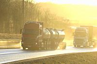 Two Volvo FH trucks, red tanker and white semi pulling freight trailer on wet road in natural, in-camera golden light. Salo, Finland. January 24, 2020...