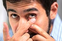 Young man putting contact lens in his left eye, close up .