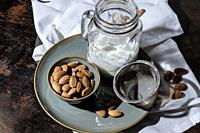 Almond vegan milk just strained into a glass jar, next to a bowl of raw almonds and a metal strainer.
