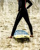 Young woman doing stretches on the beach before taking to the water to start surfing.