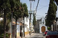 Stoned streets of Mexico City in a magical rustic town of the Assumption with the typical white walls painted with yellow in the background an 18th-ce...