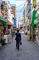 Businessman walks through a typical small street in Tokyo, Japan in summer 2019.