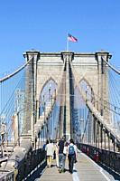 New York, New York State, United States of America. Walking towards Manhattan on the Brooklyn Bridge.