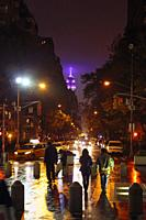New York, New York State, United States of America. Looking down 5th Avenue from Washington Square North on a rainy night. Empire State Building in ba...