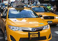 New York, New York State, United States of America. City traffic. Yellow cabs. Policeman directing traffic.