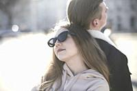 young cool woman leaning on back of boyfriend
