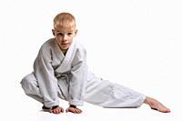 Judoka boy doing stretching at workout.