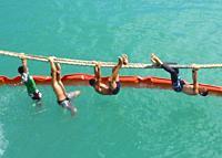 boys play on ship's rope, Hakahau harbor, Ua Pou, Marquesas, French Polynesia.