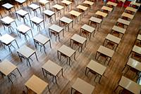 empty chairs and tables in exam room at high school