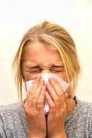 young woman sneezing in handkerchief