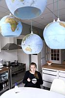 young woman starting day, eating breakfast under world globes