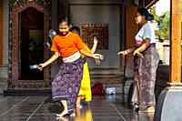 Young Balinese Girls Being Taught Traditional Dance At The Ubud Palace, Ubud, Bali, Indonesia.