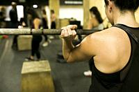 Woman Bodybuilder with heavy barbbells in gym.