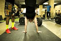 Mid adult woman upside down in a gym.