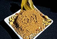 Homemade garam masala spice mix in a white small dish on a dark background close up.