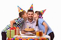 Children congratulated father on his birthday and kiss him on the cheek.
