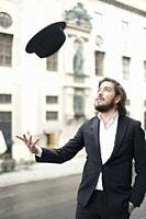 man throwing his hat in air
