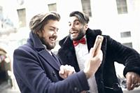 friends laughing about funny social media content seen on smartphone