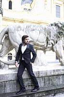stylish man exploring history of Bavaria in front of stone lion at Odeonsplatz, Munich, Germany