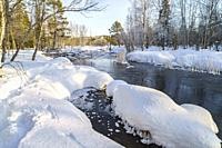 Winter landscape, creek with open water, plenty of snow in the forest, clear blue sky, Boden county, Norrbotten, Sweden.
