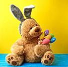 big cute brown teddy bear holding colorful Easter eggs, wearing a rabbit mask with long ears on his head, funny holiday card.