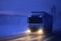 White DAF XF truck pulls semi trailer on icy road on a foggy winter evening at twilight in South of Finland. Salo, Finland. January 18, 2019.