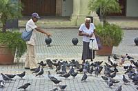 Feeding the pigeons in Plaza Vieja, Havana, Cuba.