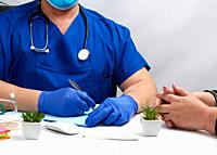 male doctor in uniform and in blue latex medical gloves sits at the table and carries out the reception of patients, workplace and office of the docto...