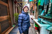 A smiling man standing at the end of an alley in Shanghai, China.