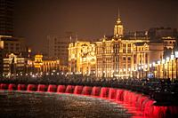 Color changing lights on the water backed by the bright glow of the Bund , Shanghai, China.