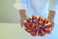 Chef holding a platter of Iberian ham.